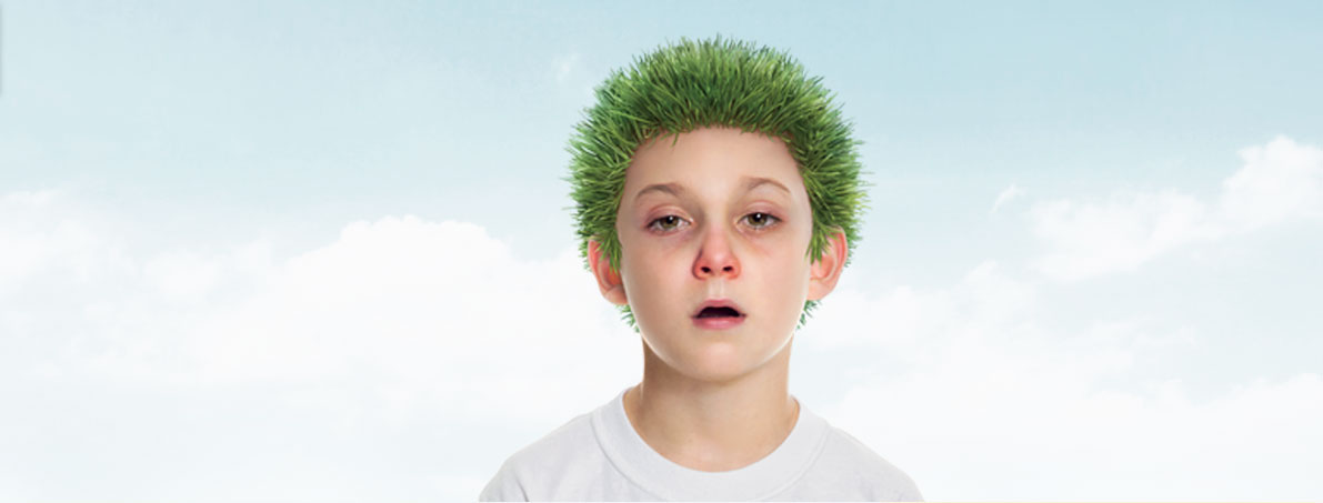 Child suffering from allergies with grass for hair